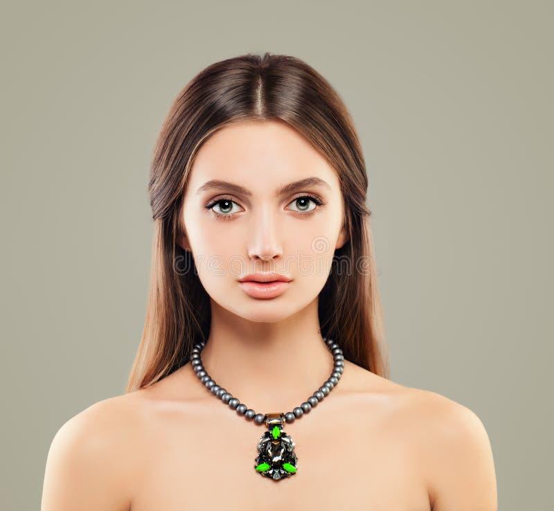 Colar vestindo da pérola da jovem mulher fotografia de stock royalty free