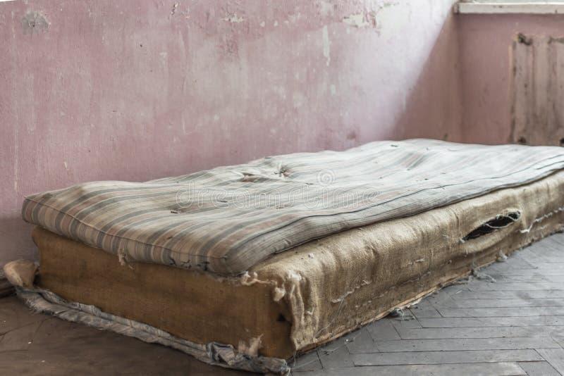 Colchão áspero velho em uma casa abandonada imagens de stock