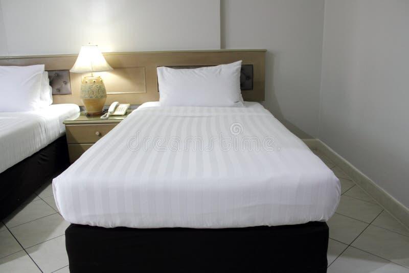 Colchón blanco y cama negra imagenes de archivo