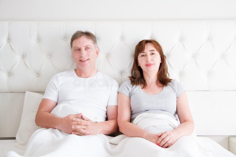 Colchón cómodo Pares de la Edad Media con las arrugas que se sientan en cama Camiseta en blanco de la plantilla Mujer y hombre en foto de archivo libre de regalías