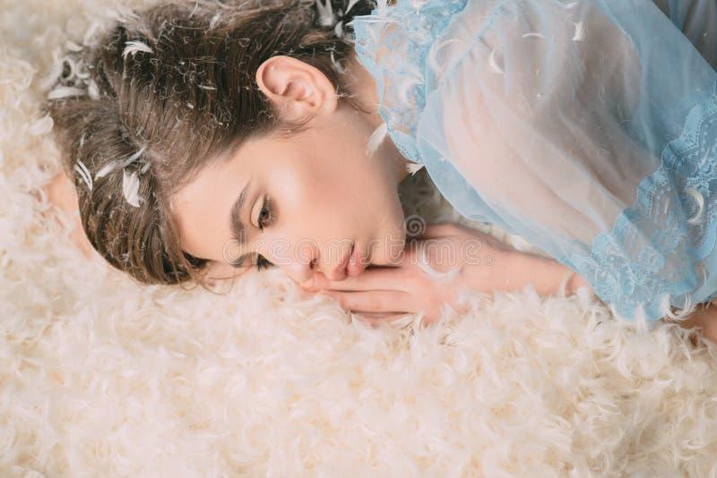 Colchón suave y que cuida Mujer joven en desgaste del sueño Muchacha linda que se relaja en la almohada y el colchón de cama de p fotografía de archivo