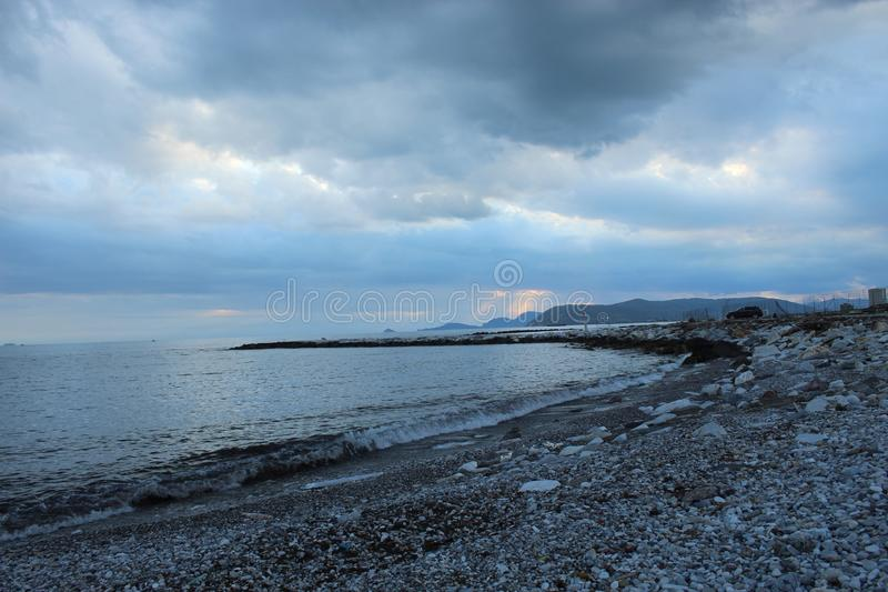 A cold afternoon at the beach with a view to the cloudy beach in Tuscany, Italy. A cloudy sky at the beach on a spring day in Italy. The sun was  not shining on stock photography