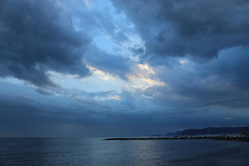 A cold afternoon at the beach with a view to the cloudy beach in Tuscany, Italy. A cloudy sky at the beach on a spring day in Italy. The sun was  not shining on royalty free stock photography
