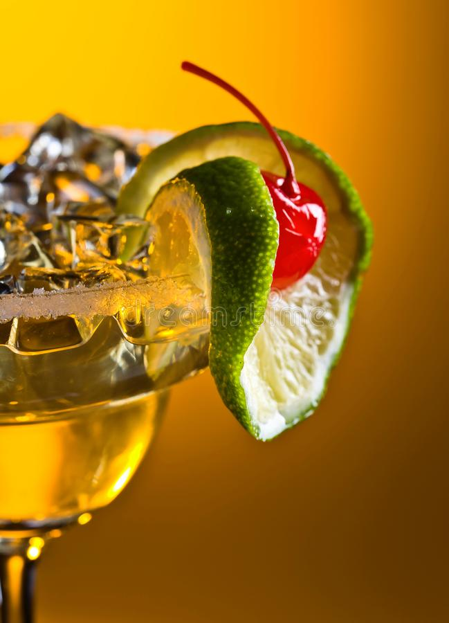 Alcoholic cocktail with cherry and lime. Cold alcoholic cocktail with ice . Cocktail garnished with cherry and lime royalty free stock image
