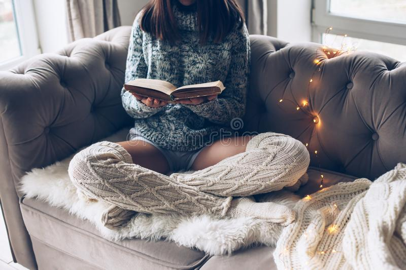 Girl reading and relaxing on a couch royalty free stock photos