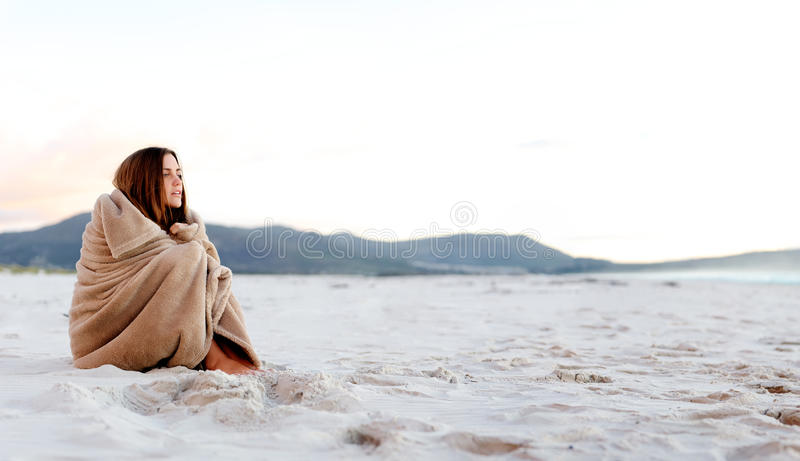 Cold beach blanket. Cold woman wraps blanket over hersolf while sitting on the beach after sunset. copyspace provided by panoramic image stock images