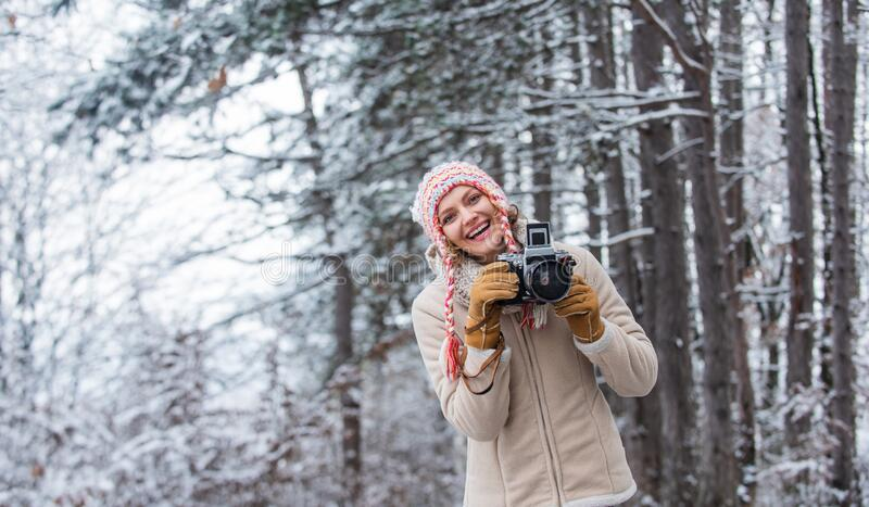 Cold and beautiful weather. happy hiker girl retro camera. professional photographer winter landscape. woman hold photo stock photo