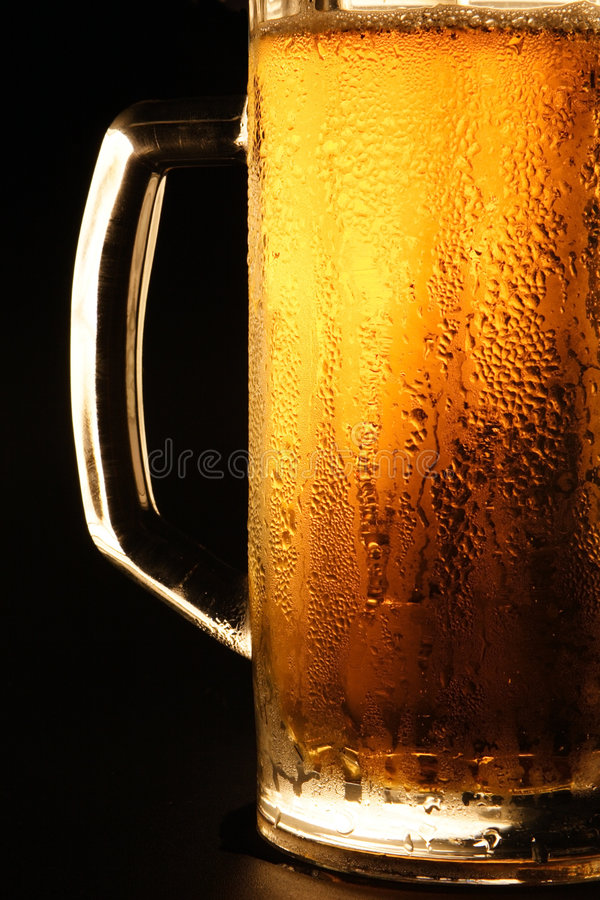 The cold beer. Mug with cold beer on a black background stock images