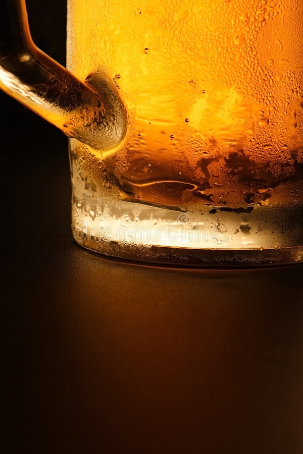 The cold beer. Mug with cold beer on a black background stock photos