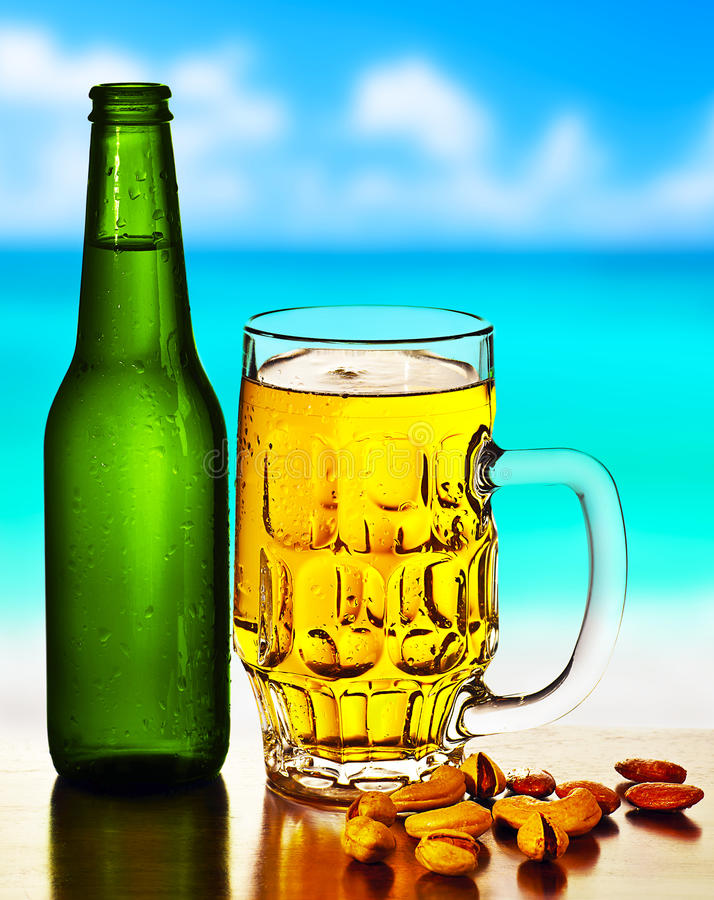Cold beer on the beach. Refreshing alcoholic drink with nuts mix, food and beverage still life, outdoor cafe, summer leisure, vacation travel and fun concept royalty free stock images