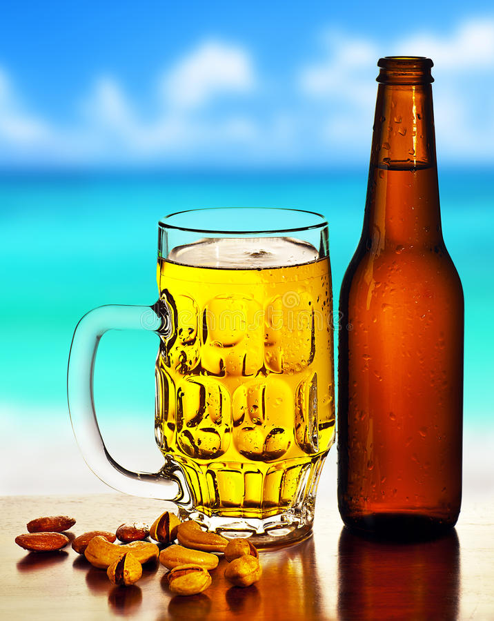 Cold beer on the beach. Refreshing alcoholic drink with nuts mix, food and beverage still life, outdoor cafe, summer leisure, vacation travel and fun concept royalty free stock photography