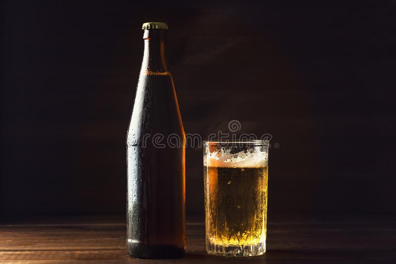 Cold beer bottle and glass with fresh beer in drops of water on dark background, craft brewery royalty free stock image