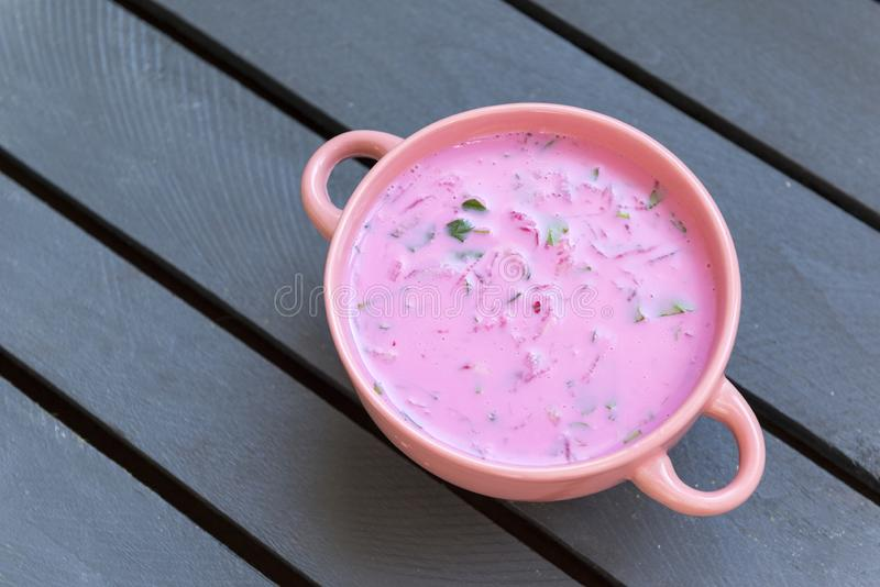 Cold beet soup in a pink bowl, pink soup. Beetroot soup; gray wooden background royalty free stock photos