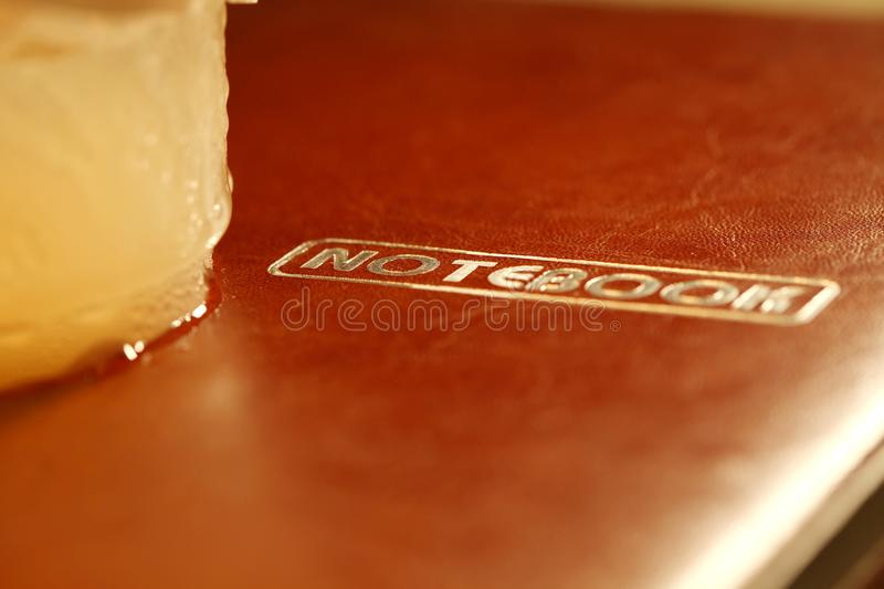 Cold beverage plastic cup put on notebook scene. royalty free stock photos