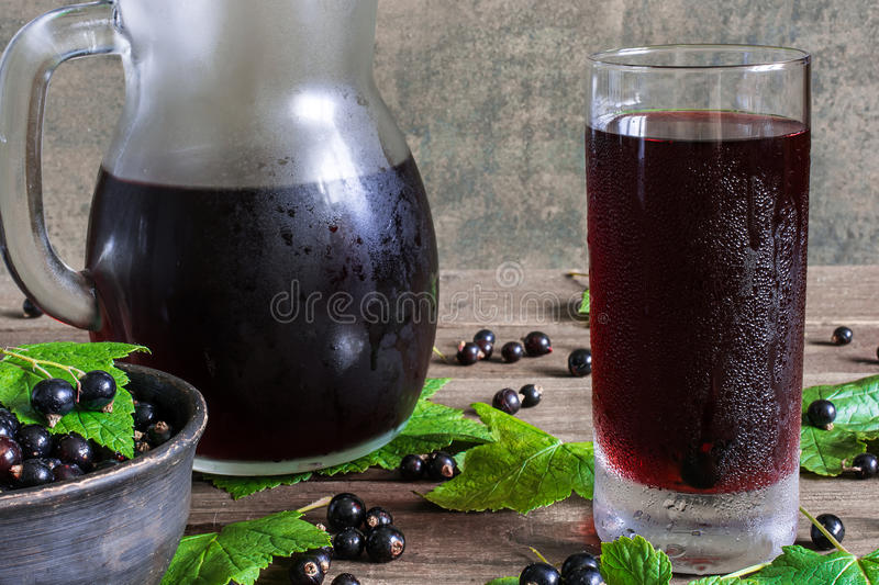 Cold black currant juice in a glass and pitcher. On rustic wooden table with ripe berries in a bowl stock photography