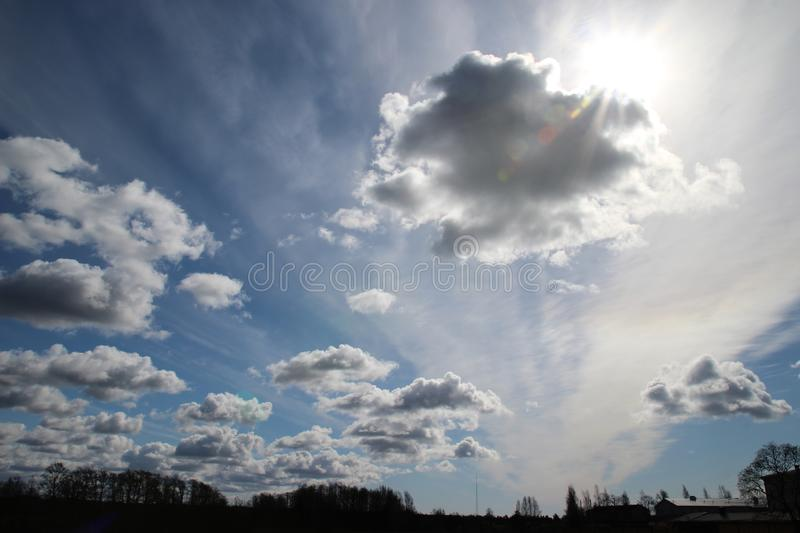 Cloud sky with sun. Cold blue cloud sky. Sun hiding behind the clouds royalty free stock photo