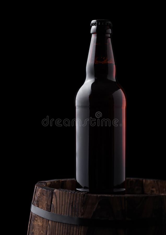Cold bottle of craft beer on old wooden barrel. On black background royalty free stock photos