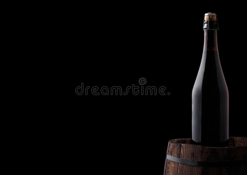 Cold bottle of craft beer on old wooden barrel. On black background stock photography