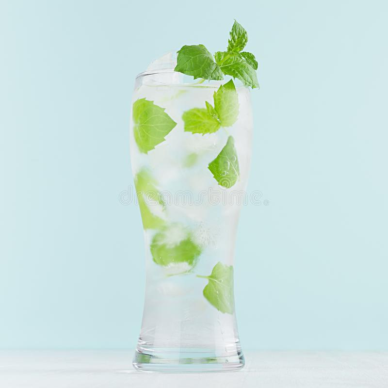 Cold bright organic cocktail with green mint, ice cubes, tonic in light soft pastel blue color background on white wood board. Cold bright organic cocktail with royalty free stock photography