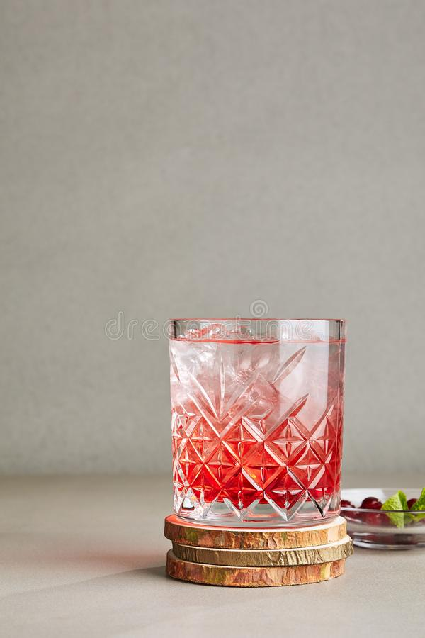 Cold Clear Drink of Red Berries with Ice, Water, Sugar in a Crystal Glass on Wooden Plate royalty free stock photo