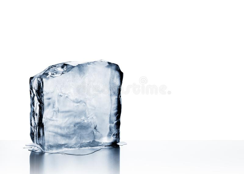 Cold clear frozen block of ice melting on white. Cold blue crystal clear frozen block of ice melting to create pool of water on scratched steel surface royalty free stock image