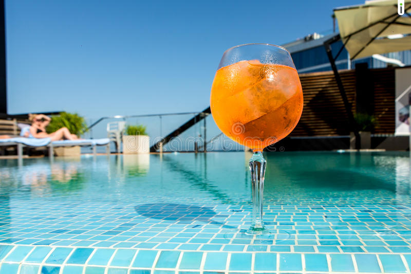Cold cocktail aperol spritz on the edge of the pool. Against the sky royalty free stock image
