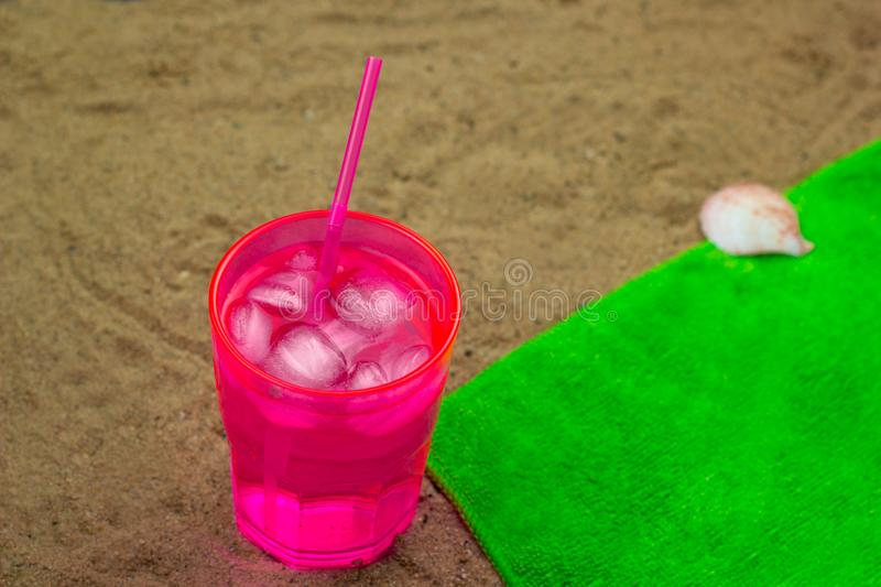 Cold cocktail on a green towel on a beach royalty free stock photography