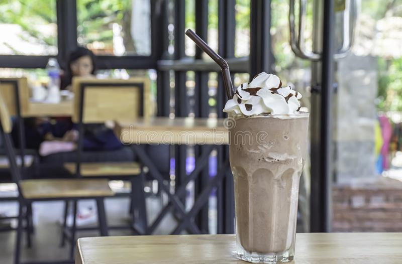 Cold cocoa with whipped cream on top of the glass on wooden table Background glass windows and  tree stock photos