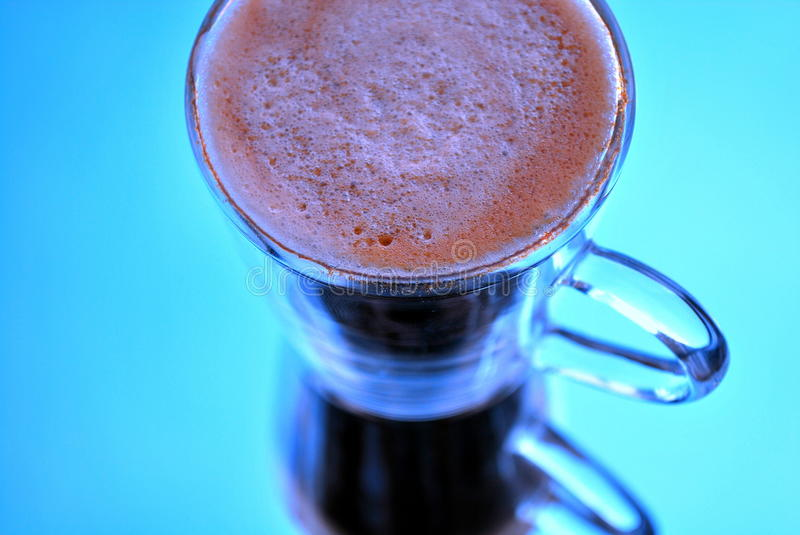 Cold Coffee. A mirror image of a glass of coffee in blue royalty free stock photo