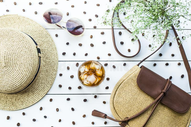 Cold coffee among summer accessories. Cold coffee in a glass with ice. On the table among coffee beans and summer women`s accessories. Summer relax concept. Flat stock photography