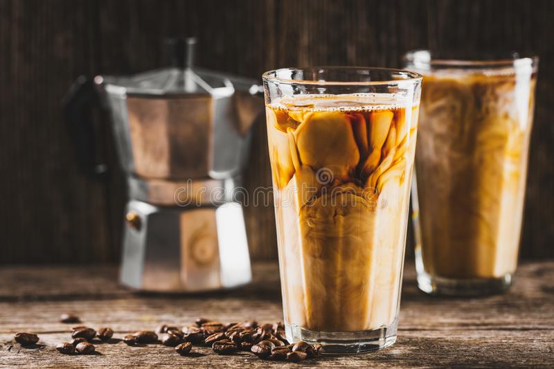 Cold coffee with ice and cream. Tasty appetizing refreshing cold coffee with ice and cream milk in glasses. Ready for drinking. Served on old wooden table stock photos