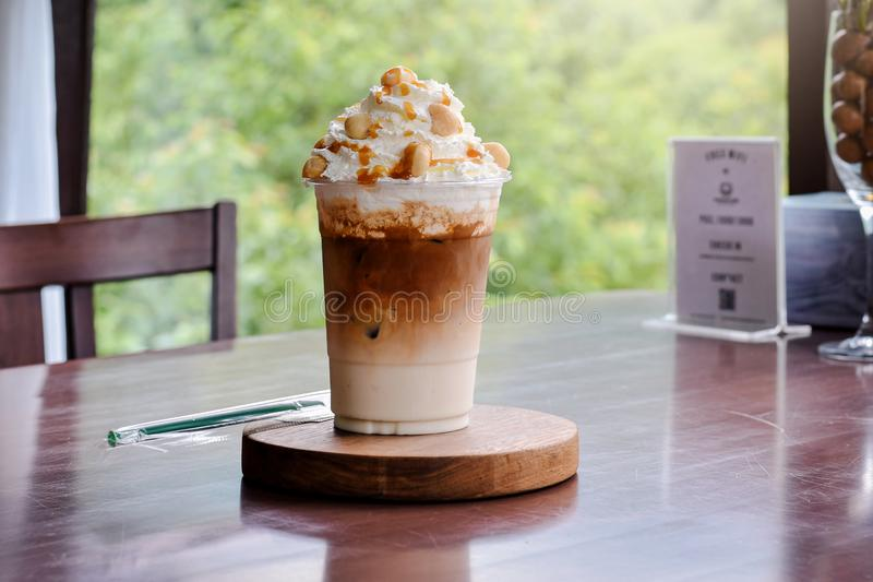 Cold coffee -Iced Caramel Macchiato Layered espresso drink, vanilla syrup, cold creamy milk espresso. On wood table stock image