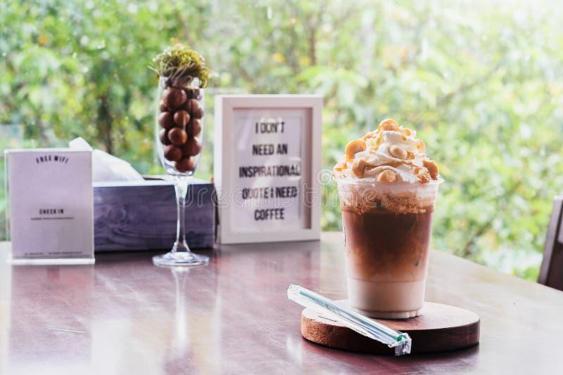 Cold coffee -Iced Caramel Macchiato Layered espresso drink, vanilla syrup, cold creamy milk espresso. On wood table royalty free stock photo