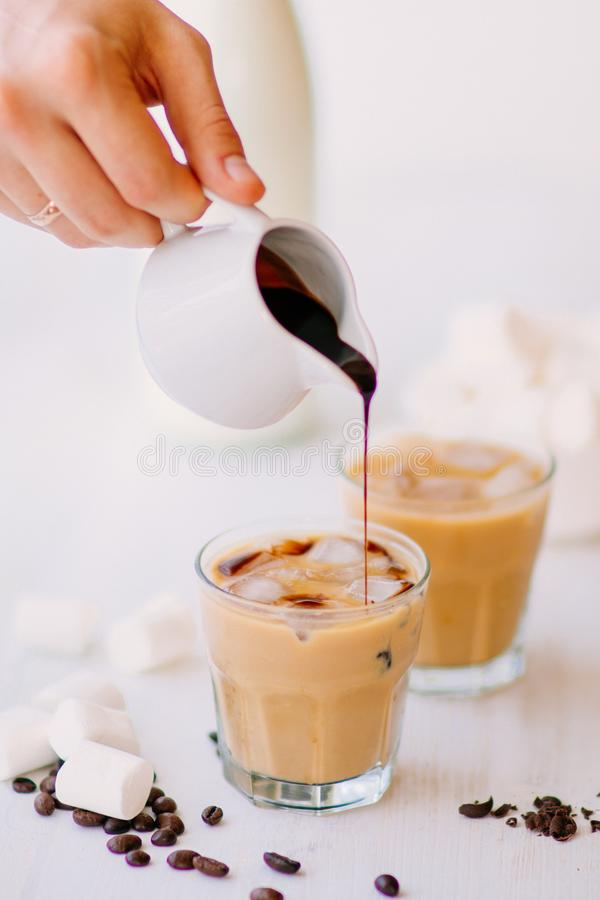 Cold coffee with milk and chocolate. Light background. Iced coffee. Concept of a cooling drink. Marshmelow and coffee beans on the table. Summer drink stock image