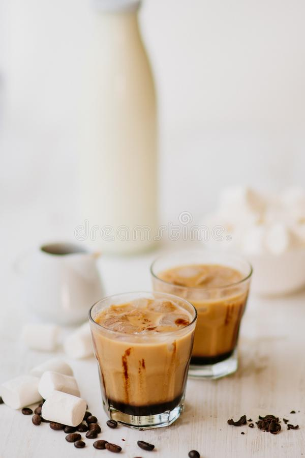 Cold coffee with milk and chocolate. Vertical shot. Light background. Iced coffee. Marshmelow and coffee beans on the table. Concept of a cooling drink. Summer royalty free stock photography