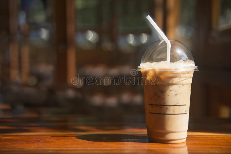 Cold coffee in plastic cup on brown wooden table at cafe. stock photos