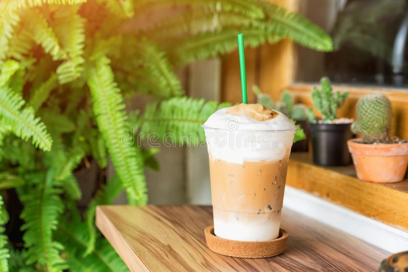Cold coffee in plastic cup on wooden table at cafe. royalty free stock photography