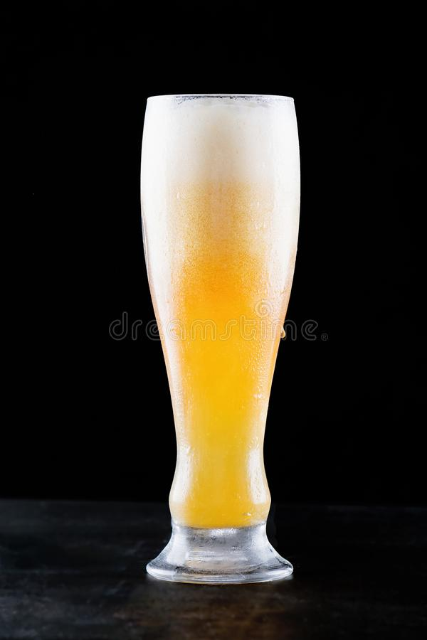 Glass of fresh cold light beer with froth flowing on the table and beautiful spilled beer on a black background stock image