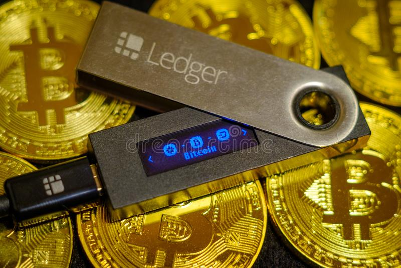 Cold crypto wallet Ledger Nano S lying on golden bitcoin coins stock photos