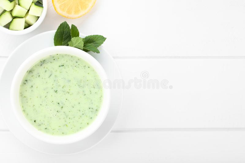 Cold Cucumber, Yogurt, Mint and Lemon Soup. Refreshing cold cucumber, yogurt, mint and lemon soup in bowl, photographed overhead on white wood Selective Focus royalty free stock photo