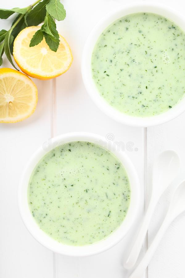 Cold Cucumber, Yogurt, Mint and Lemon Soup. Refreshing cold cucumber, yogurt, mint and lemon soup in bowls, photographed overhead on white wood Selective Focus royalty free stock photography