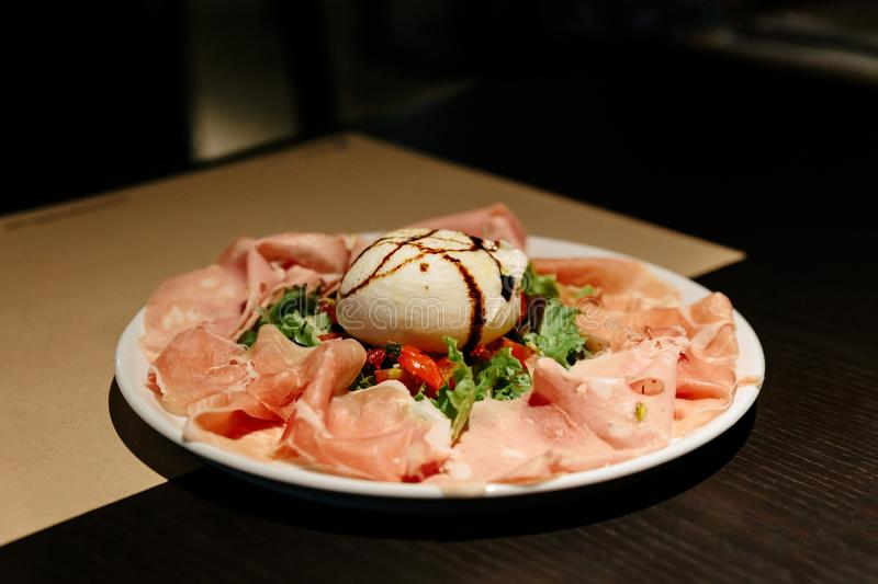 Cold Cuts Burratina: Burrata Cheese served with Parma Ham, Mortadella and Salad. Served in white plate on paper mat stock photography