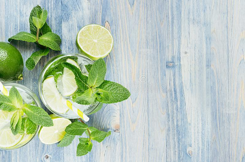 Cold detox summer mineral water with lime, mint, ice, straw on soft blue wood background as decorative border, top view. Cold detox summer mineral water with stock photo