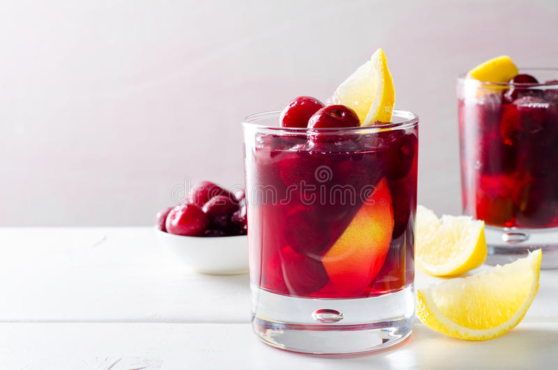 Cold drink with cherry and lemon in glasses, on white wooden background. Horizontal stock photos