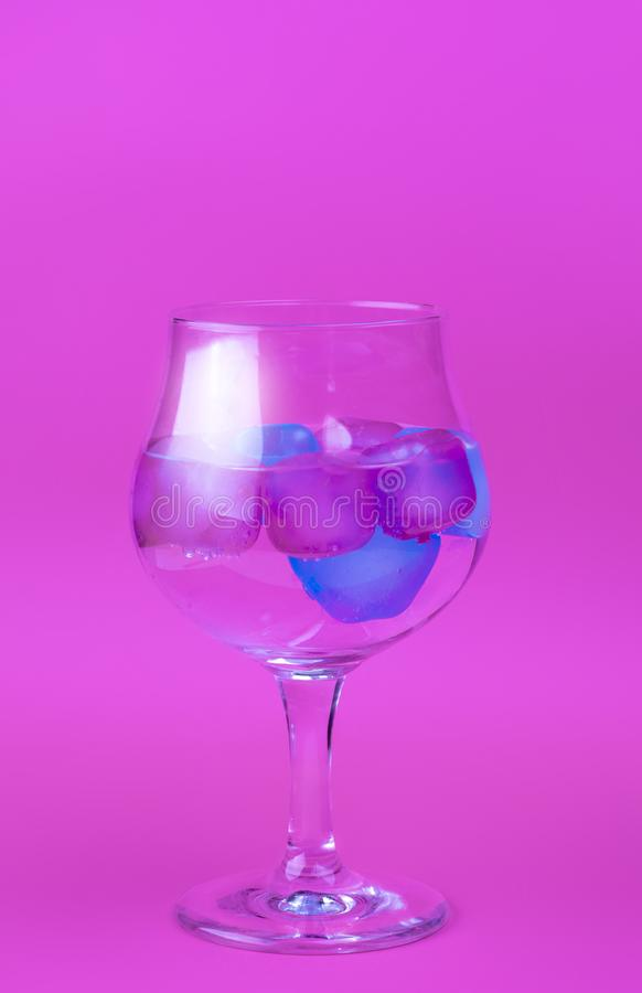 A cold drink with colorful pink and blue ice in a wine glass on a bright pink background. Summer concept horisontal image stock photography