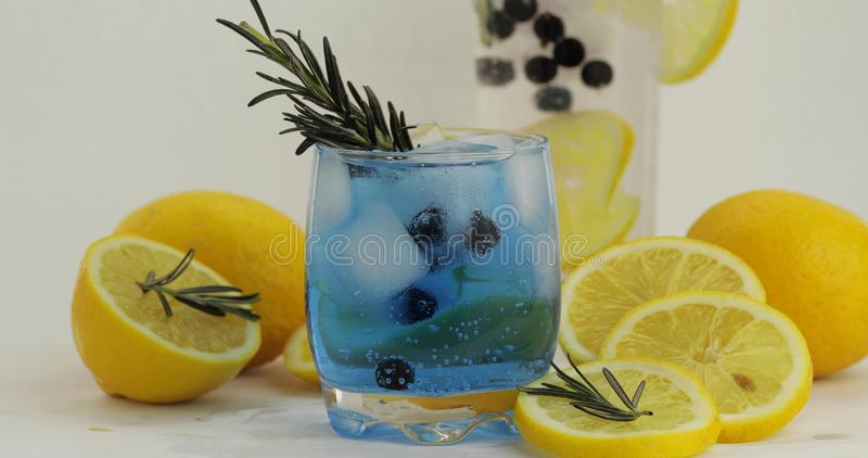 Cold drink in drinking glass. Refreshing soda lemonade blue cocktail with lemon stock images