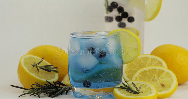 Cold drink in drinking glass. Refreshing soda lemonade blue cocktail with lemon royalty free stock photography