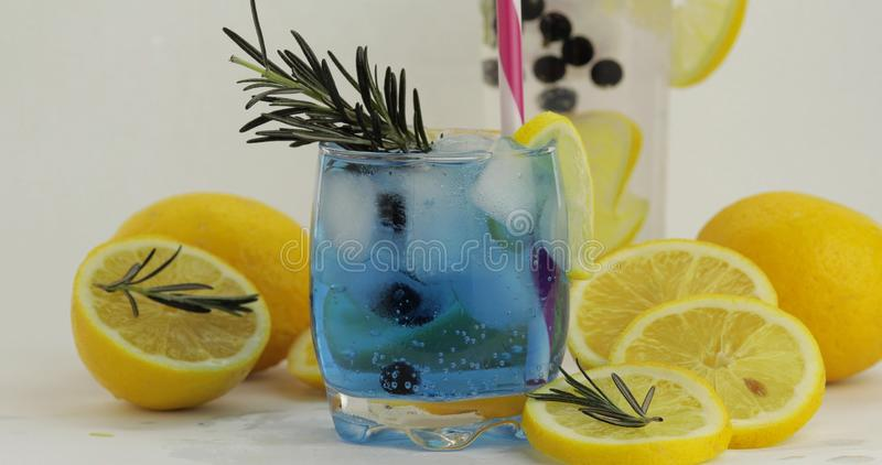 Cold drink in drinking glass. Refreshing soda lemonade blue cocktail with lemon royalty free stock images