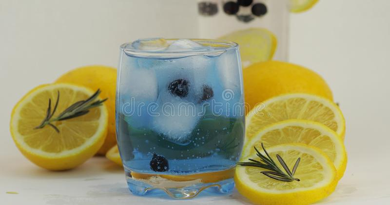 Cold drink in drinking glass. Refreshing soda lemonade blue cocktail with lemon stock image