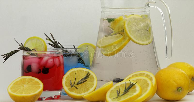 Cold drink with lemon, ice cubes and black currant in a jar glass stock images
